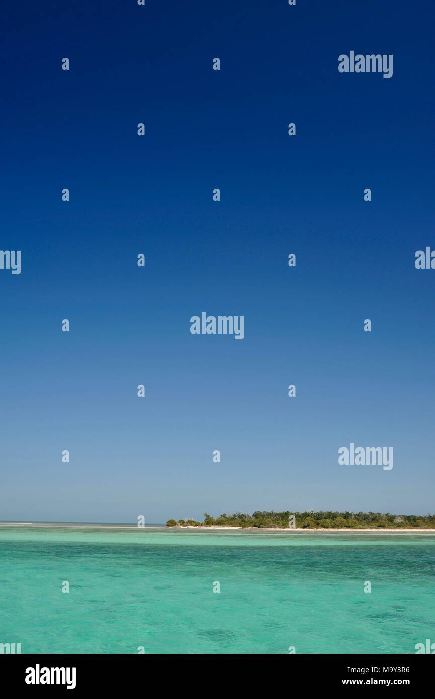 Distant white sandy beach-rimmed island with clear blue sky and turquoise waters near Key West, Florida, USA - Stock Image