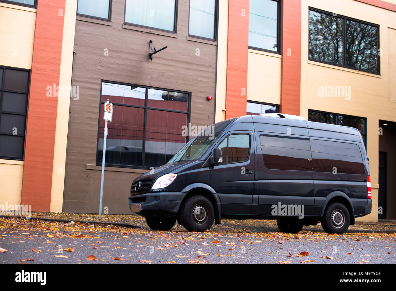 Black commercial mobile compact agile cargo minivan for small business and local delivery stand on the urban city street at industrial zone in front o - Stock Image