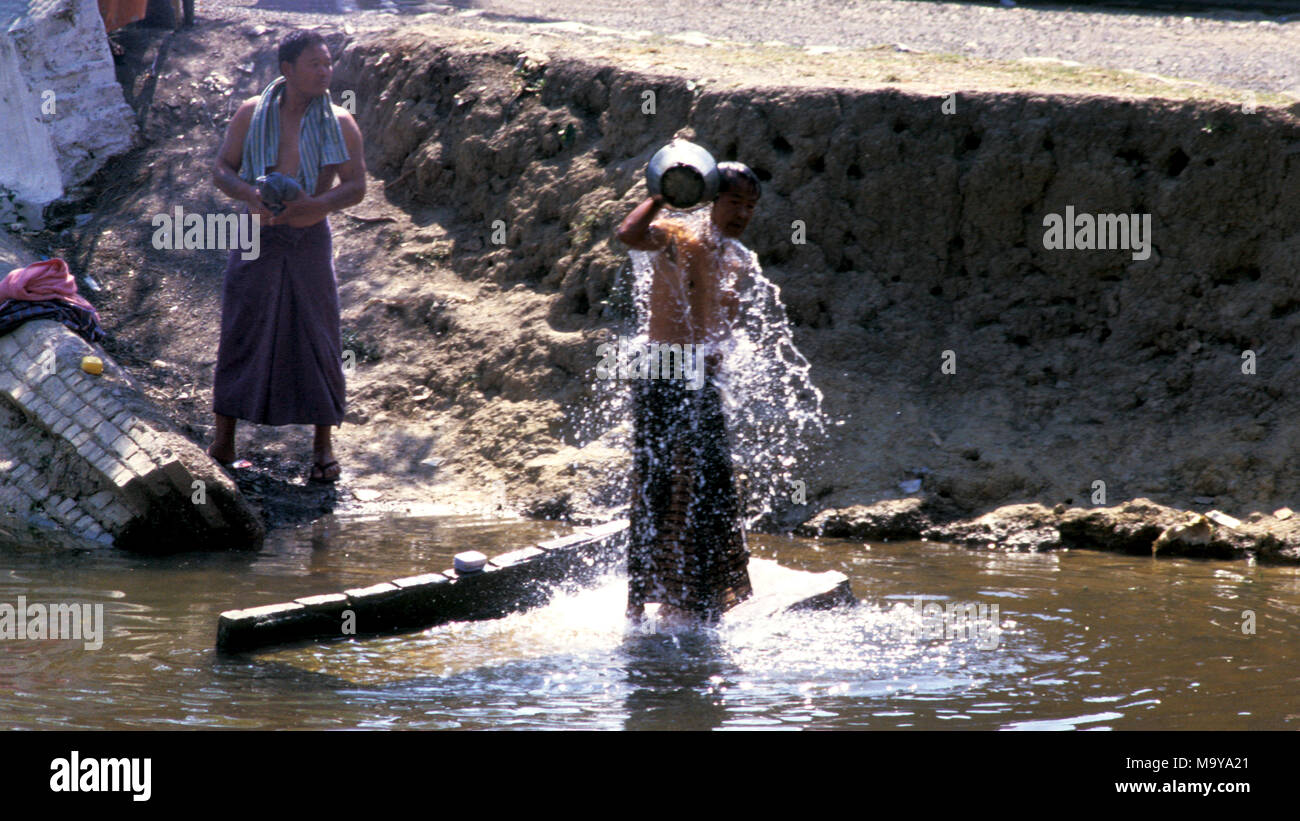 Indigenous Shan men washing themselves in their village river. Shan State, Myanmar (Burma). - Stock Image