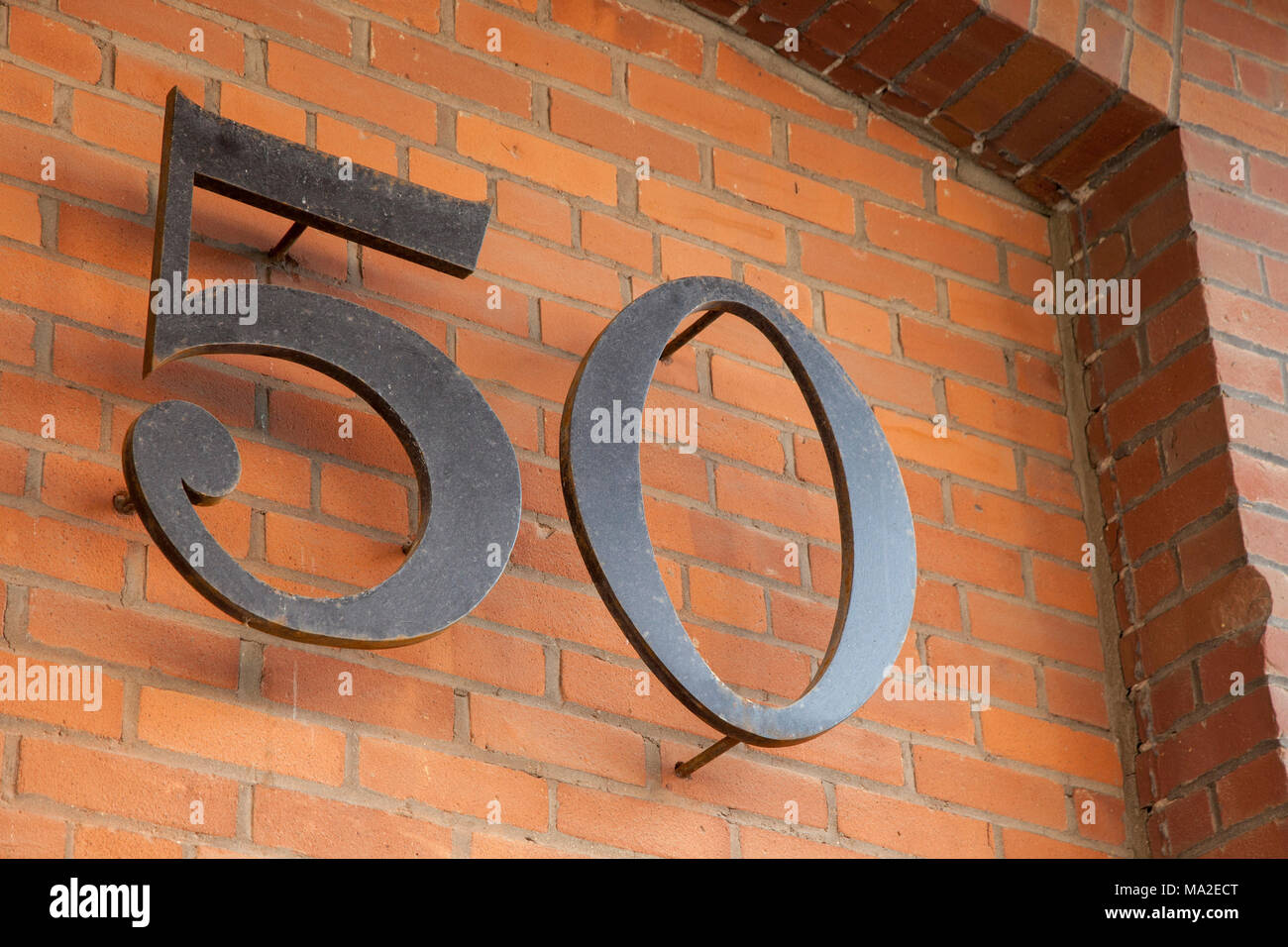 Number 50 Cut From Steel On Brick Wall