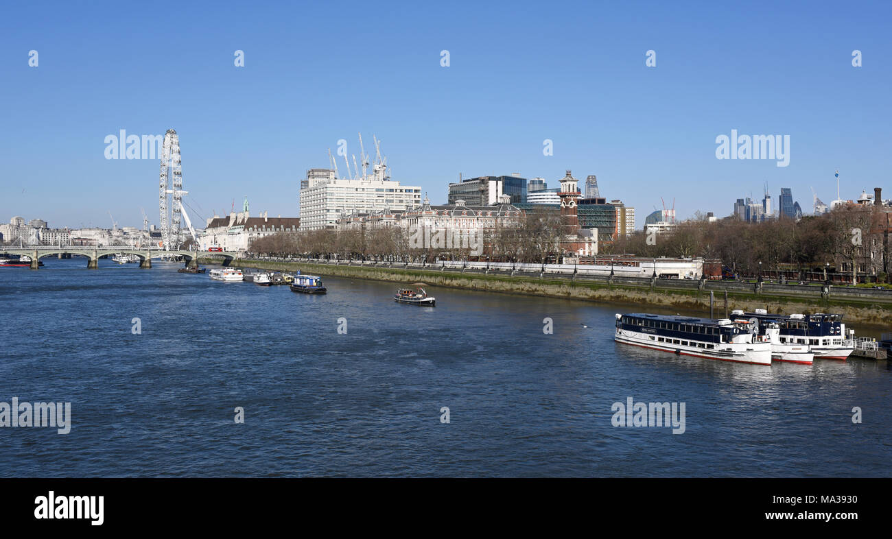 Boats moored on the River Thames in front of Westminster Bridge, The London Eye and St Thomas' Hospital, London - Stock Image