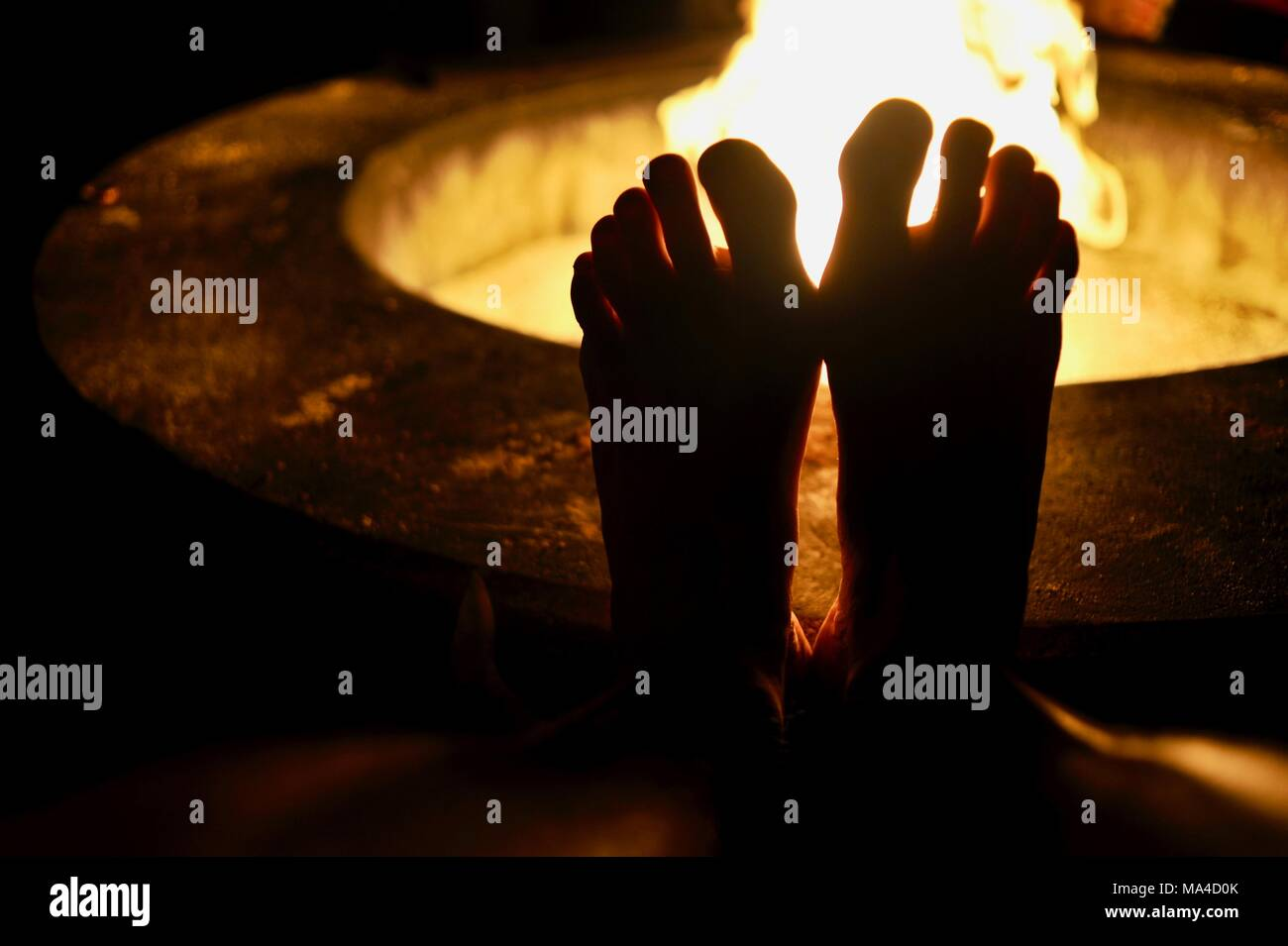 Man resting his bare feet on the cement fire pit ring with flickering flames in outdoor fire pit along pier in Florida Keys, USA - Stock Image