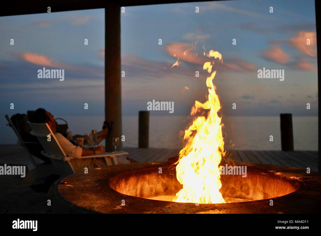 Flickering flames in outdoor fire pit along pier in Florida Keys, USA - Stock Image