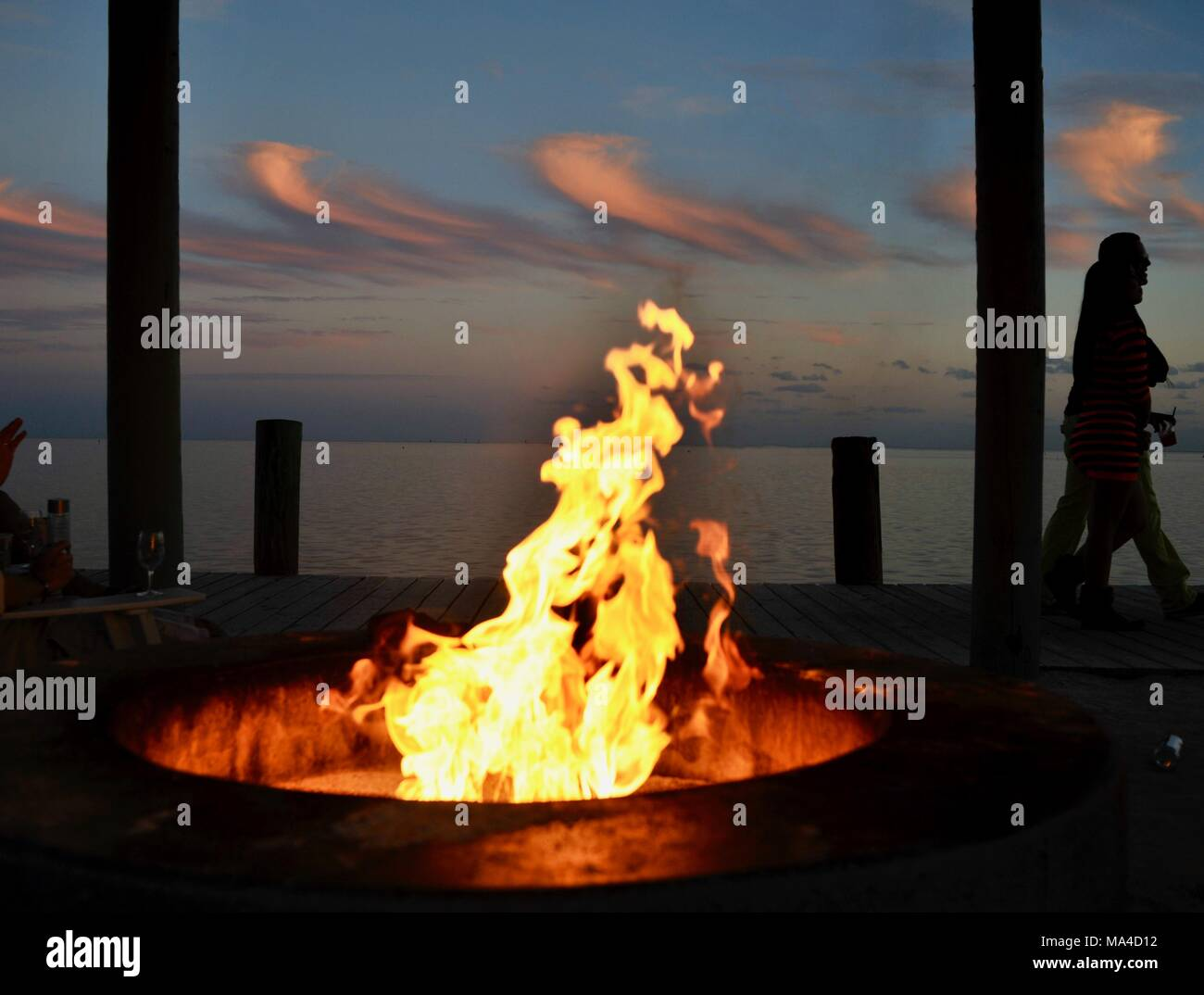 Flickering flames in outdoor fire pit along pier with couple walking by, in Florida Keys, USA - Stock Image