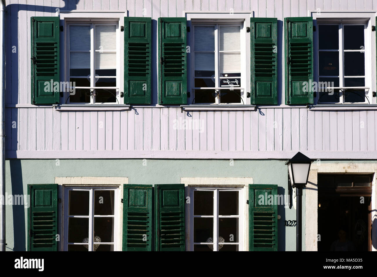 Terraced house with nostalgic wooden shutters and a lantern, - Stock Image