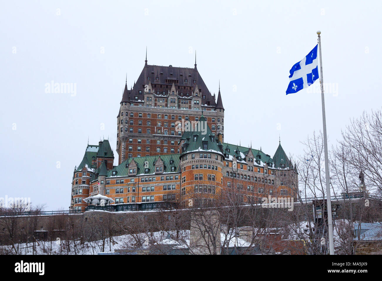 View of Frontenac Castel (Chateau de Frontenac, in French) in winter under the snow with a Quebec flag waiving. The Château Frontenac is a grand hotel - Stock Image