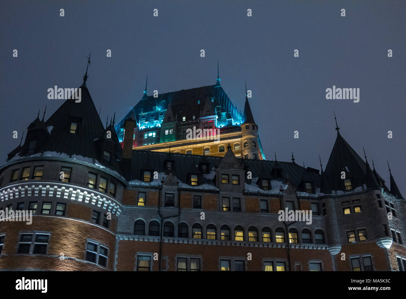 View of Frontenac Castle (Chateau de Frontenac, in French) in winter under the snow during a cold evening. The Château Frontenac is a grand hotel in Q - Stock Image