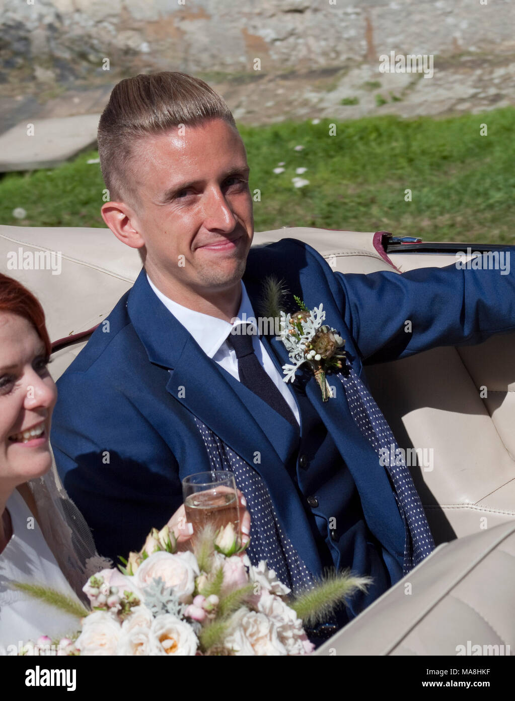 Newly married groom leaving in an open car and a blue suit - Stock Image