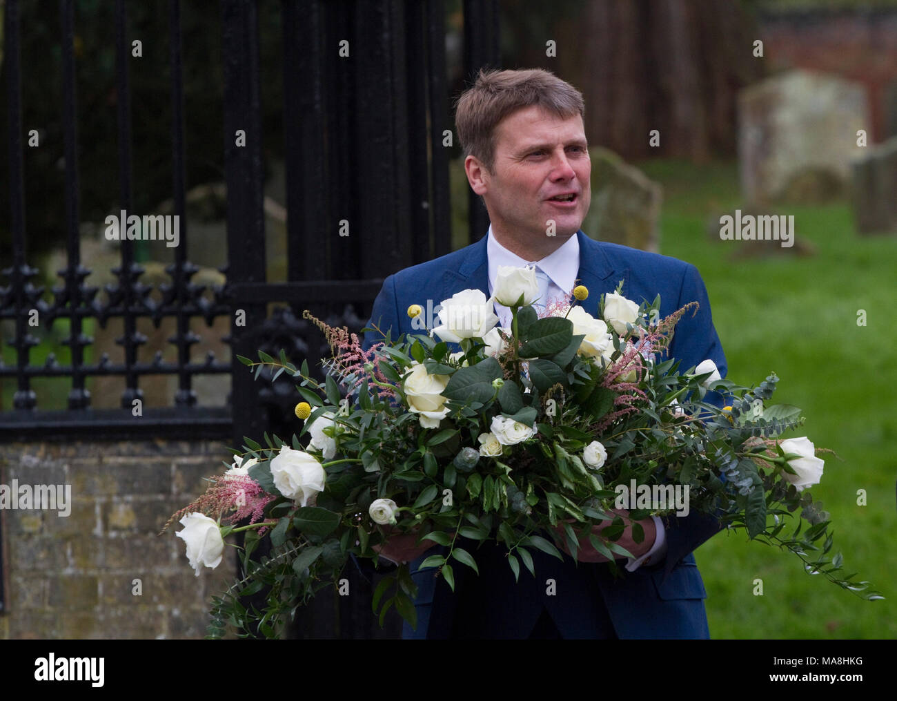 Man leaving church wedding carrying a floral arrangement - Stock Image