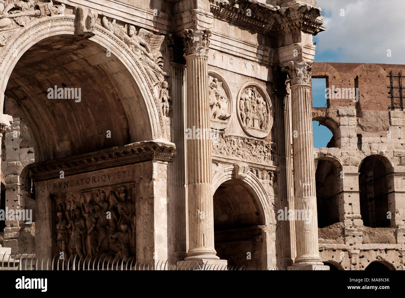 Ornate facade of the Arch of Constantine, Arco di Costantino, and the Colosseum Rome - Stock Image
