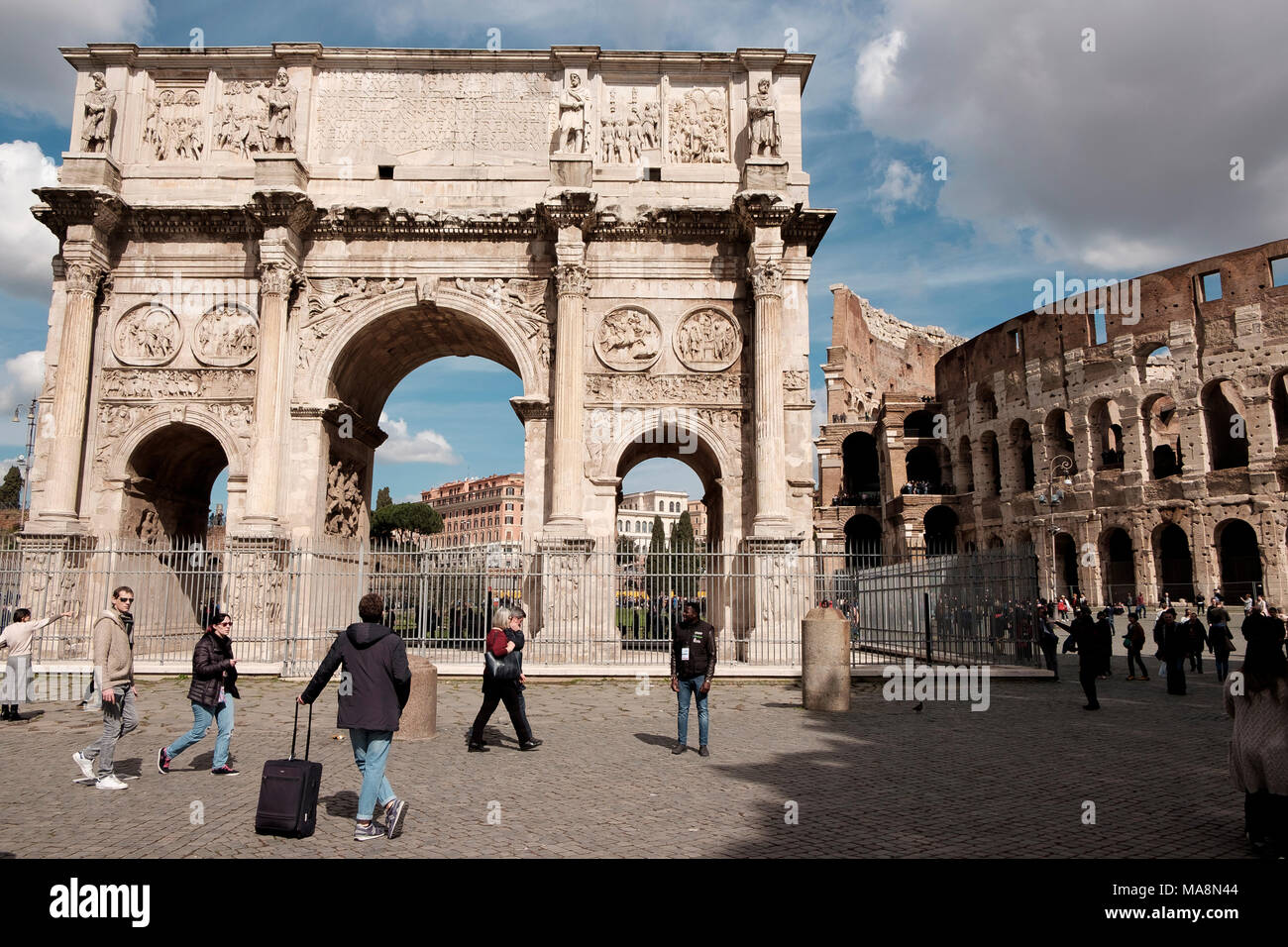A tourist with a suitcase admires the Arch of Constantine, Arco di Costantino, Rome - Stock Image