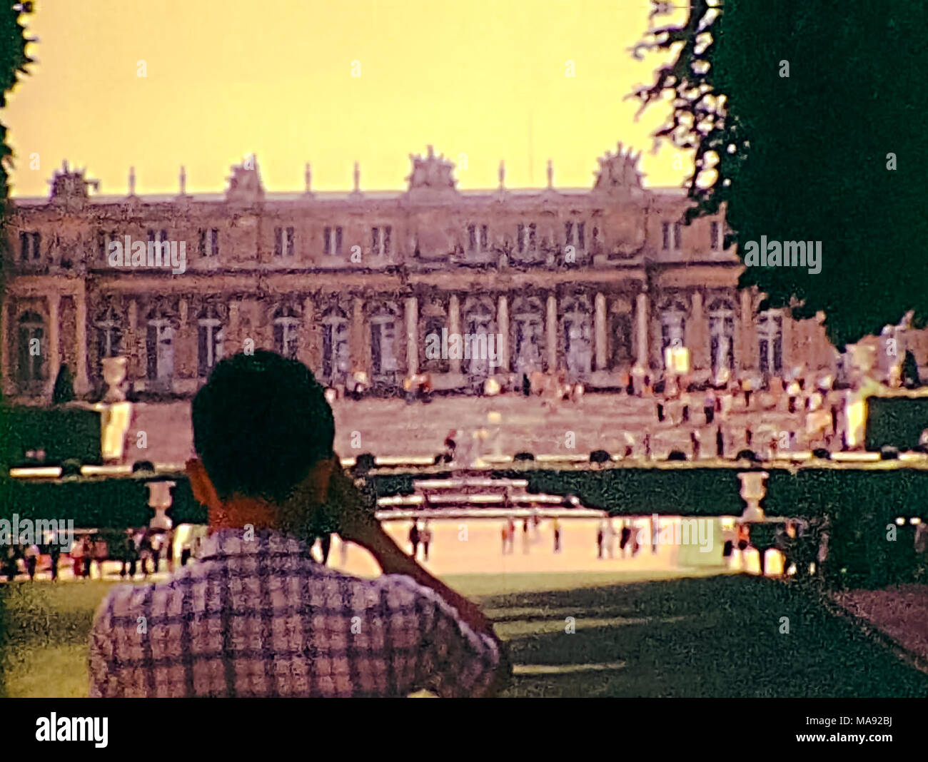 PARIS, FRANCE - CIRCA 1976: Tourists looking the Palace of Versailles from the Versailles garden. Historic archival footage in Paris city of France in 1970s. - Stock Image