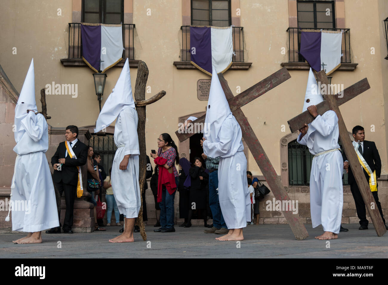 Queretaro, Mexico, 31 Mar 2018. Hooded penitents carry wooden crosses as they begin the Procession of Silence through the streets on Good Friday during Holy Week March 30, 2018 in Querétaro, Mexico. The penitents, known as Nazarenes, carry the heavy crosses and drag chains in a four hour march in memory of the passion of Christ. Credit: Planetpix/Alamy Live News - Stock Image