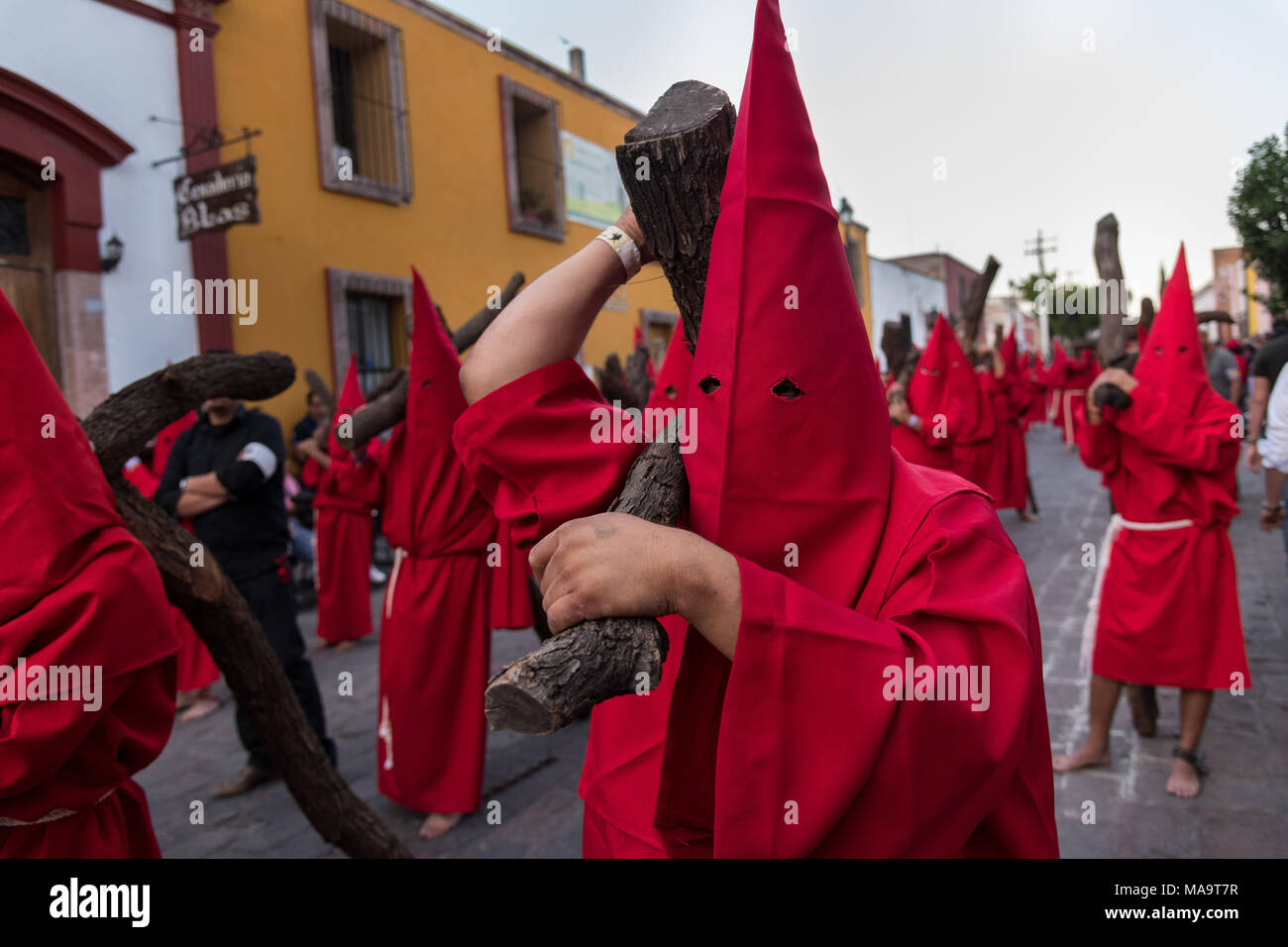 Queretaro, Mexico, 31 Mar 2018. Hooded penitents carry wooden crosses during the Procession of Silence through the streets on Good Friday during Holy Week March 30, 2018 in Querétaro, Mexico. The penitents, known as Nazarenes, carry the heavy crosses and drag chains in a four hour march in memory of the passion of Christ. Credit: Planetpix/Alamy Live News - Stock Image