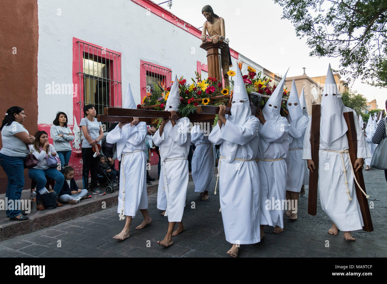 Queretaro, Mexico, 31 Mar 2018. Hooded penitents carry a statue of Jesus during the Procession of Silence through the streets on Good Friday during Holy Week March 30, 2018 in Querétaro, Mexico. The penitents, known as Nazarenes, carry heavy crosses and drag chains in a four hour march to relive the pain and suffering during the passion of Christ. Credit: Planetpix/Alamy Live News - Stock Image