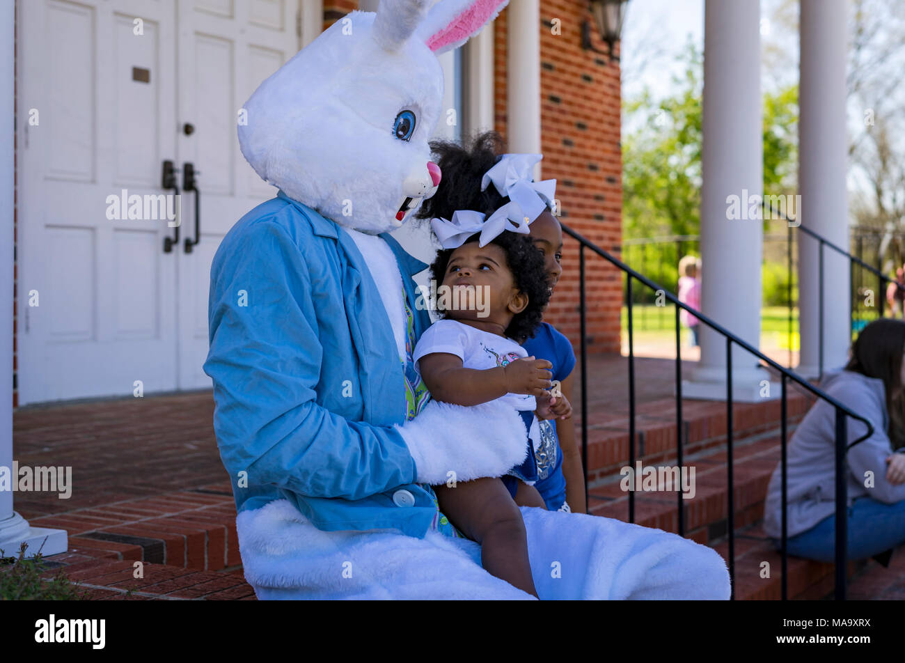 Alabama, USA, 31 Mar 2018. 11-month-old Aniyla Walker, looking at the easter bunny, was not too sure what to think of this large rabbit. Aniyla's older sister, Arya who is six, didn't seem to mind at all. The kids were at the Easter Egg Hunt in Vernon, Alabama with their mother, Aleea. The event was held Saturday, March 31st 2018. Credit: Tim Thompson/Alamy Live News - Stock Image
