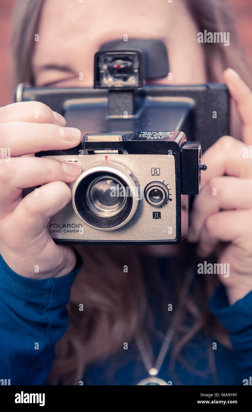 Teenage girl using an original Polaroid instant camera - Stock Image