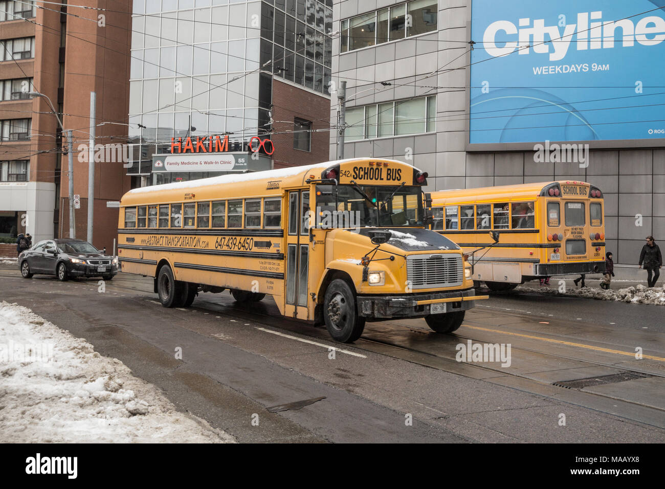 TORONTO, CANADA - DECEMBER 20, 2016: Freightliner FS 65 school bus on service in a residential part of downtown Toronto, another yellow school bus can - Stock Image