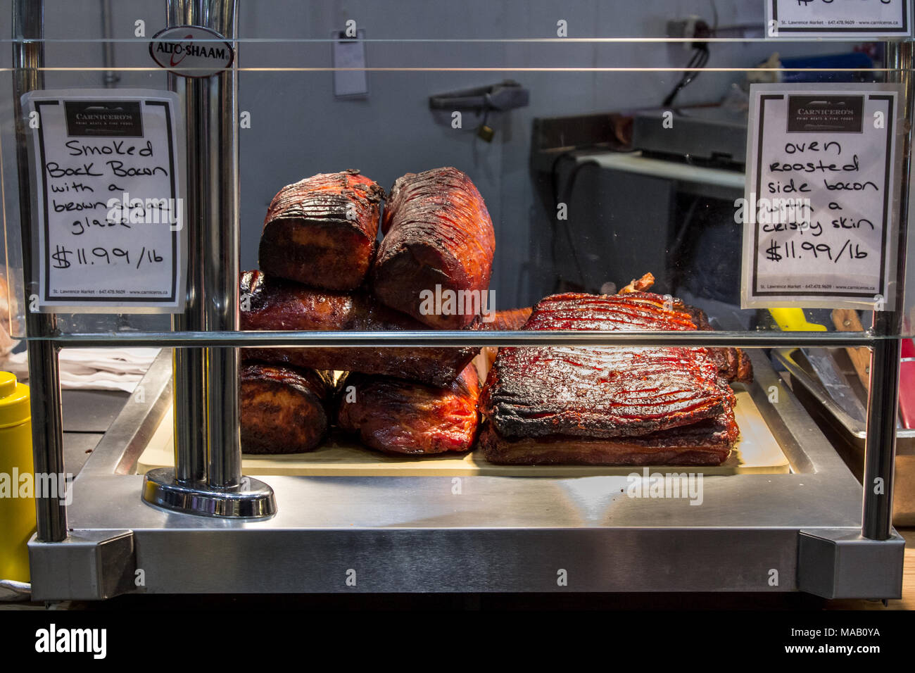 TORONTO, CANADA - DECEMBER 21, 2016: Canadian bacon, also known as peameal, for sale, grilled and cooked, on a shop in St Lawrence Market, downtown To - Stock Image