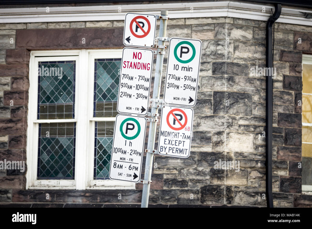 Typical North American no parking signs with detailed instructions on the parking regulations taken in Toronto, Ontario, Canada  Picture of Parking an - Stock Image
