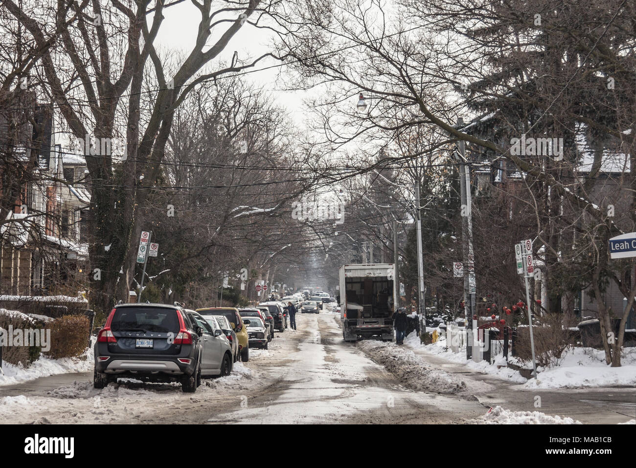 TORONTO, CANADA - DECEMBER 21, 2016:Typical North American suburban street in the suburbs of Toronto, Ontario, during a snowy afternoon, cars parked n - Stock Image