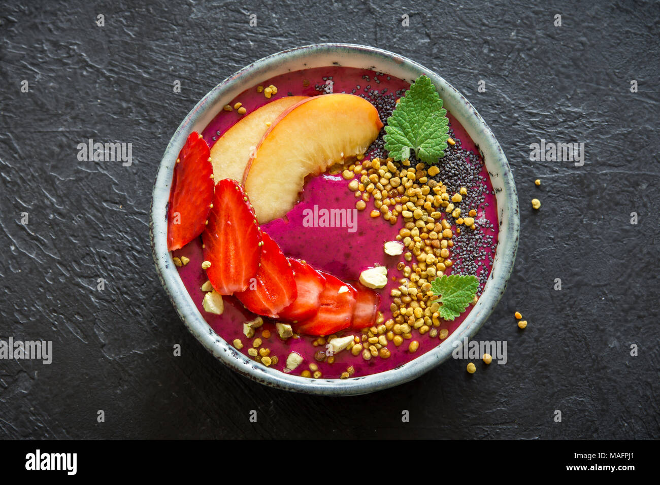 Acai smoothie bowl with chia seeds, fruits, berries (strawberries) and bee pollen for healthy vegan vegetarian diet raw breakfast. Breakfast smoothie Stock Photo