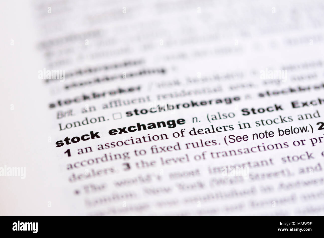 a macro shot showing the definition of the word stock exchange in an