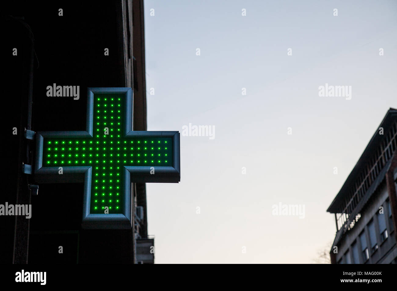 Pharmacy green cross lit with neon and LED lights in sunset. This cross is a universal symbol for pharmacy in Europe  Picture of a green cross indicat - Stock Image