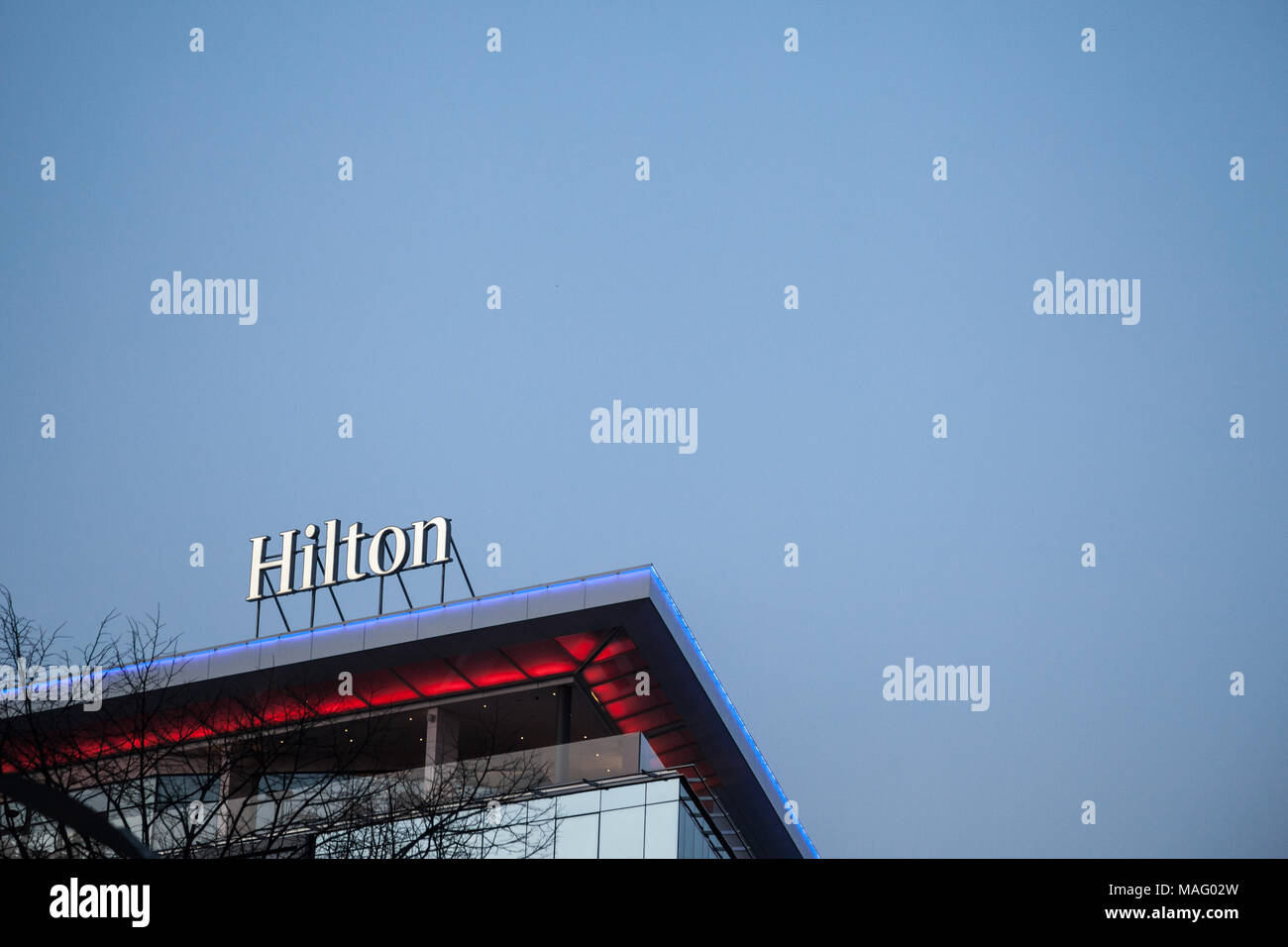 BELGRADE, SERBIA - MARCH 25, 2018: Hilton logo lit on their newly opened hotel of Belgrade, during the evening. Hilton is one of the biggest brands of - Stock Image
