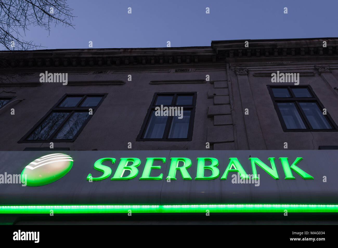 BELGRADE, SERBIA - MARCH 25, 2018: Sberbank logo lit on a subsidiary of Belgrade, during the evening. Sberbank is one of the biggest banks of Russia,  - Stock Image