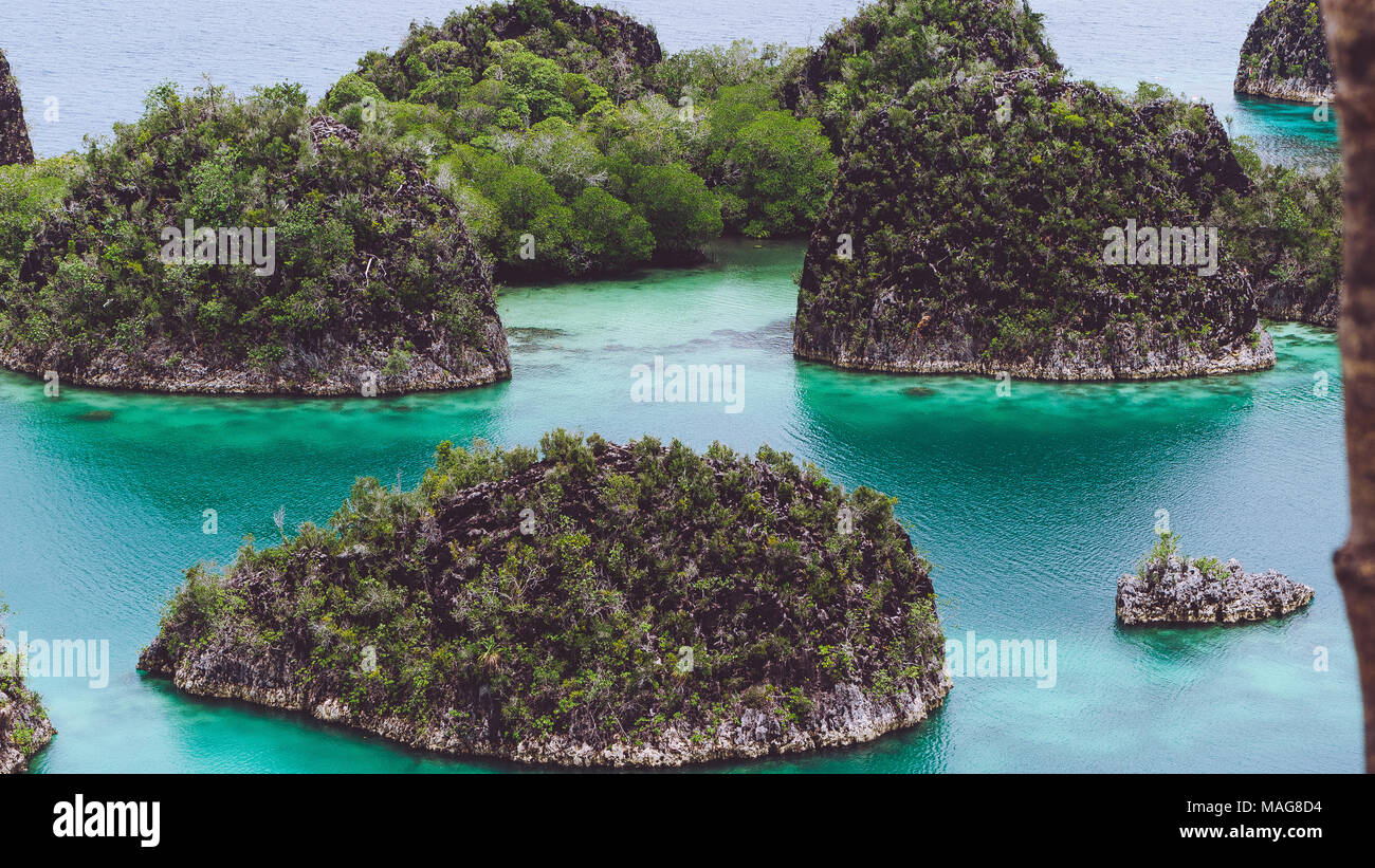 Painemo, Group of small island in shallow blue lagoon water, Raja Ampat, West Papua, Indonesia - Stock Image