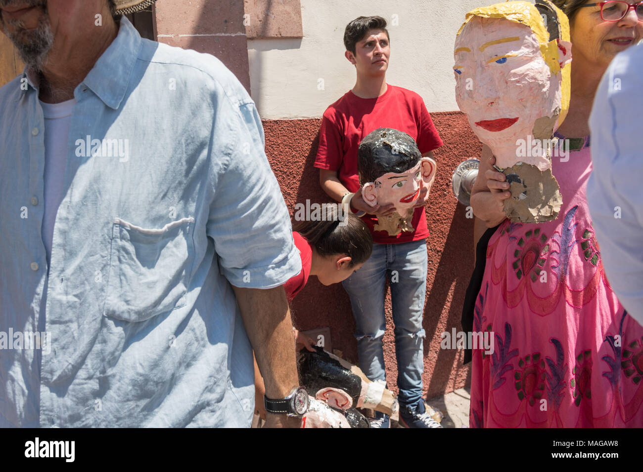 People walk away with the head of an effigy of U.S. President Donald Trump after it was exploded during the Burning of Judas Easter-time ritual marking the end of Holy Week April 1, 2018 in San Miguel de Allende, Mexico. While the tradition includes burning a paper effigy of Judas a recent popular addition has been paper doll caricatures of Donald Trump across Mexico. - Stock Image