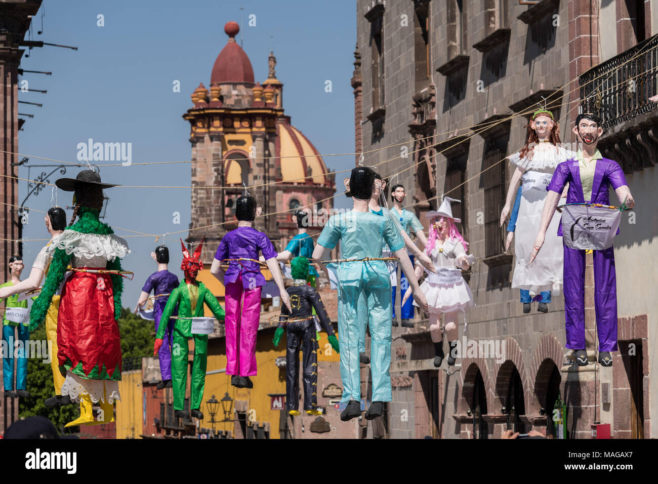 Paper doll effigies hang in the Plaza Allende in preparation for the Burning of Judas Easter-time ritual marking the end of Holy Week April 1, 2018 in San Miguel de Allende, Mexico. - Stock Image