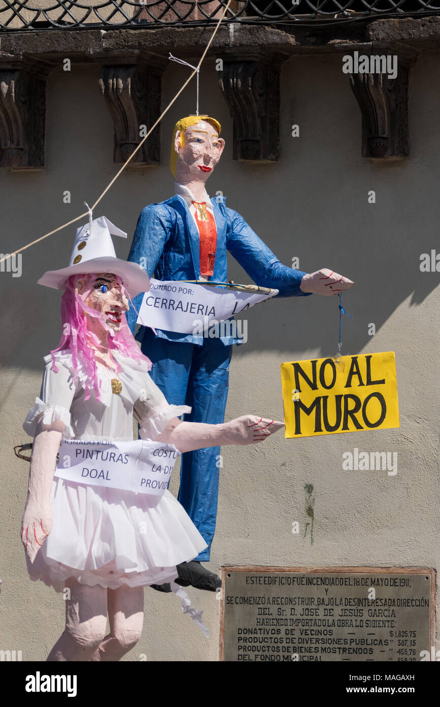 An effigy of U.S. President Donald Trump hangs in the Plaza Allende with other paper dolls in preparation for the Burning of Judas Easter-time ritual marking the end of Holy Week April 1, 2018 in San Miguel de Allende, Mexico. While the tradition includes burning a paper effigy of Judas a recent popular addition has been paper doll caricatures of Donald Trump across Mexico. The doll is holding a sign saying 'No Wall' in reference to the Trump border wall. - Stock Image