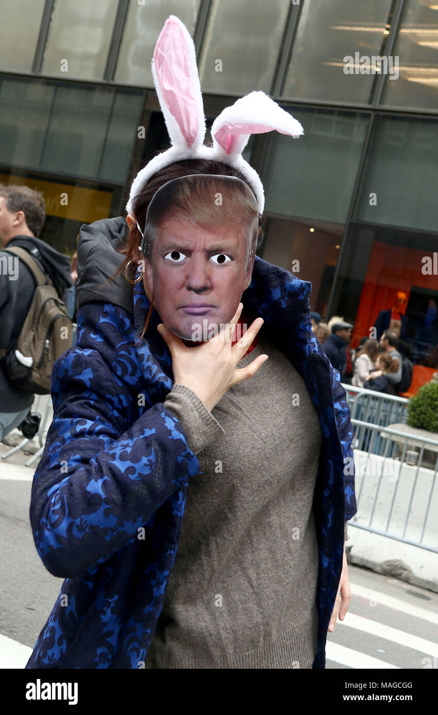 New York City, New York, USA. 1st Apr, 2018. A parade goer wears a Donald Trump mask and bunny ears at the 2018 Easter Parade held on 5th Avenue. The Easter tradition of wearing fancy bonnets and costumes dates back to 1870's New York. Credit: Nancy Kaszerman/ZUMA Wire/Alamy Live News - Stock Image