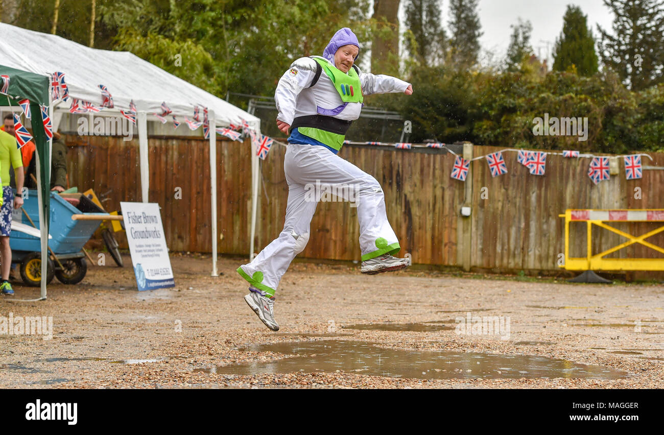 Bolney Sussex UK 2nd April 2018  - Simon Cowen dressed as Buzz Lightyear leaps across a puddle at the annual Bolney Pram Race today which is held at the Eight Bells pub in the village every Easter Bank Holiday Monday raising money for local charities SERV Sussex and Age UK Photograph taken by Simon Dack Credit: Simon Dack/Alamy Live News - Stock Image