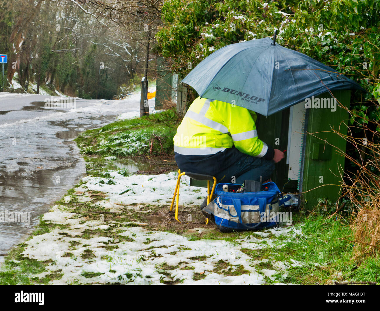 Ashbourne, Derbyshire. 2nd Apr, 2018. UK Weather: BT OpenReach Engineer working in poor conditions after 1' of morning snow quickly melts causing flooding on Easter Bank Holiday Monday in Ashbourne, Derbyshire Credit: Doug Blane/Alamy Live News - Stock Image