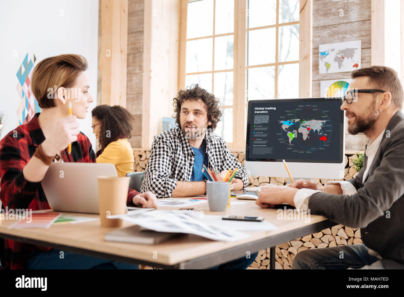 Serious man discussing work his co-workers - Stock Image