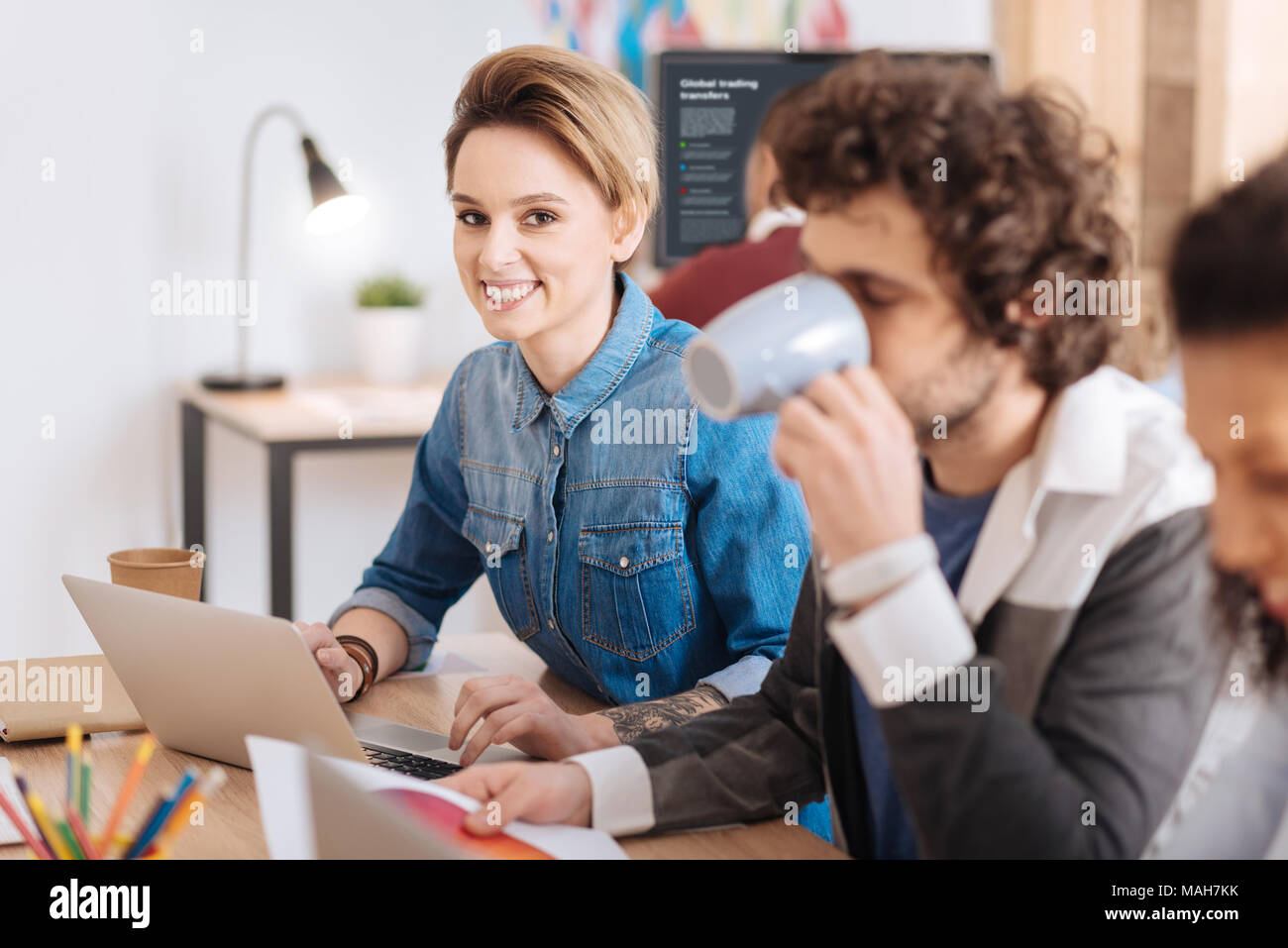 Alert woman working with her co-workers - Stock Image