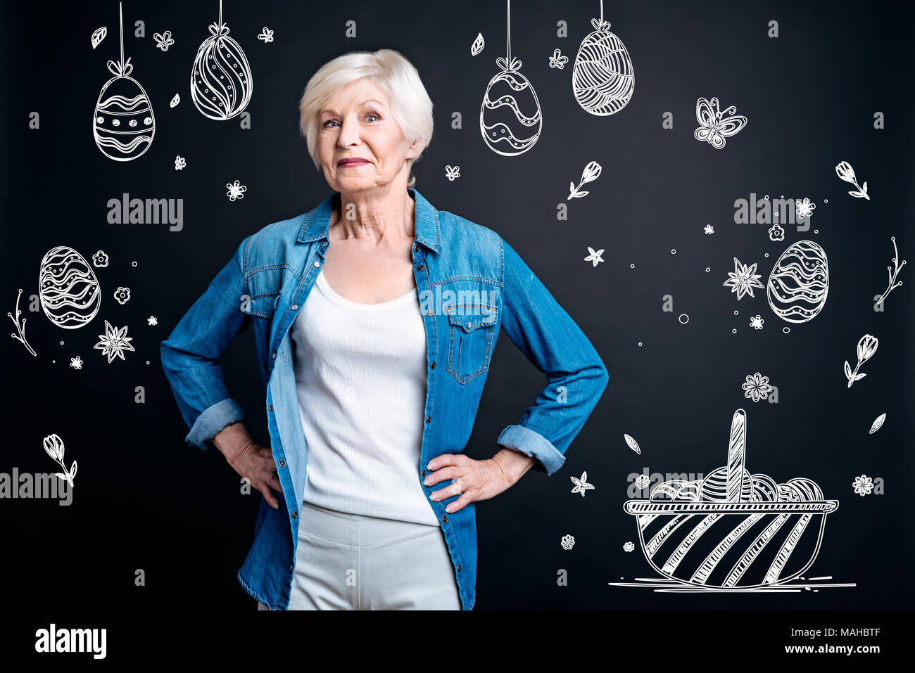 Emotional woman standing with her hands on hips and waiting for Easter - Stock Image