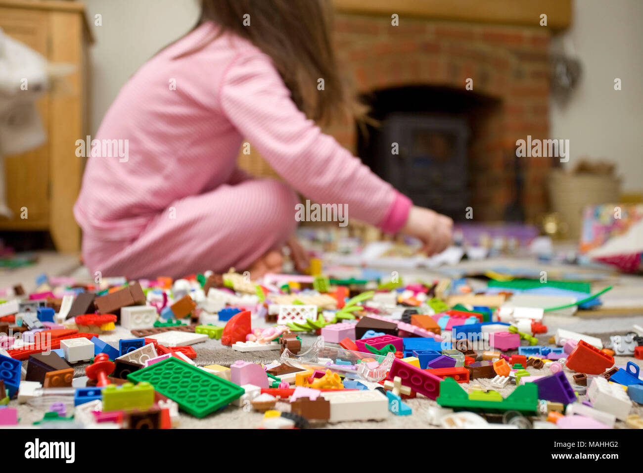 Child sat on floor playing with lego Stock Photo