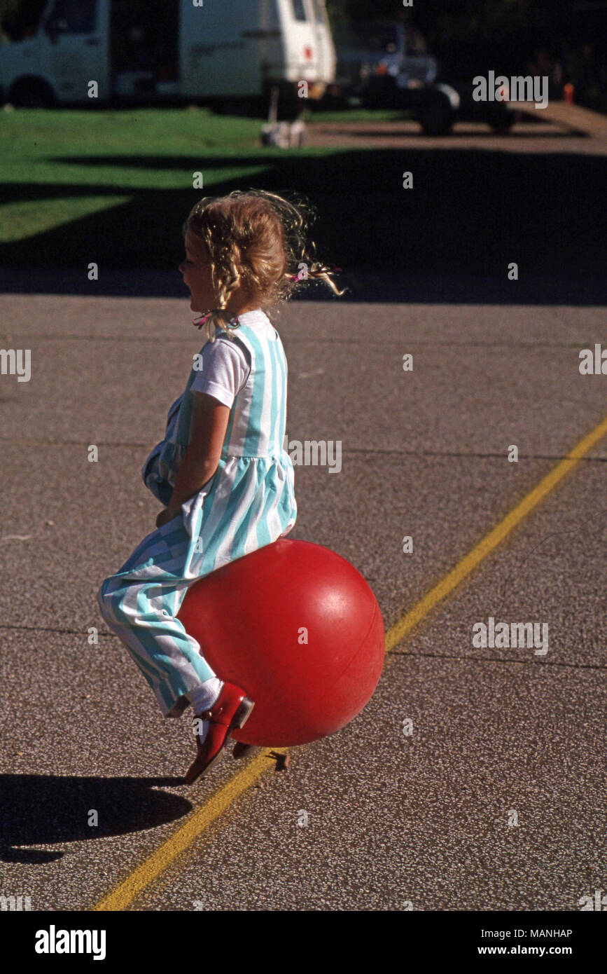 Girl playing on bouncy ball with handles - Stock Image