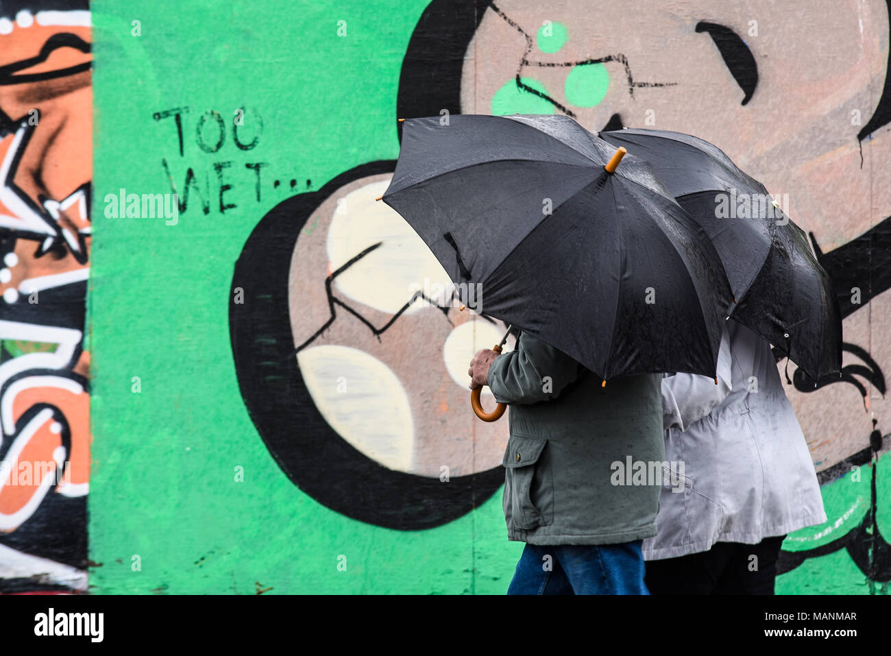 too-wet-bank-holiday-weather-in-southend-on-sea-essex-uk-couple-with-umbrellas-in-the-rain-walking-past-graffiti-wall-with-too-wet-for-literal-use-MANMAR.jpg