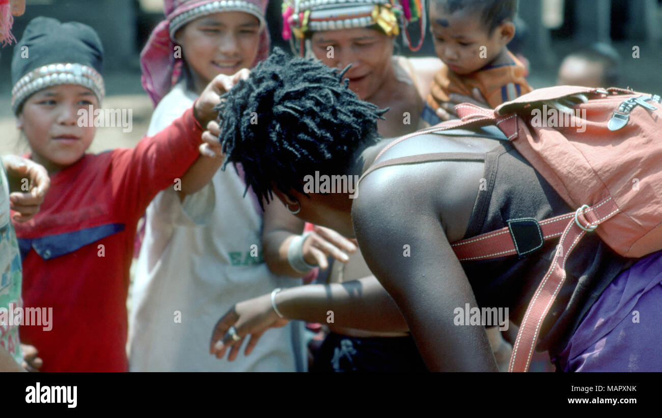 In an indigenous Akha village in northen Laos, the inhabitants are curious during their first encounter with a person with black skin. - Stock Image