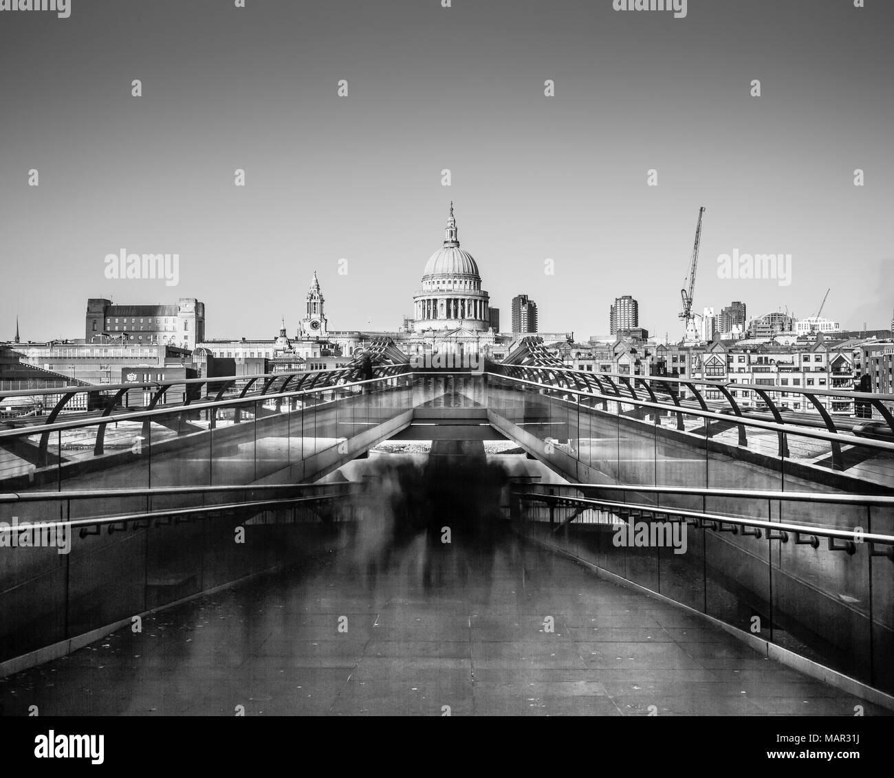 Ghostly figures going to work in long exposure image of St. Paul's from Millennium Bridge, City of London, London, England, United Kingdom, Europe - Stock Image