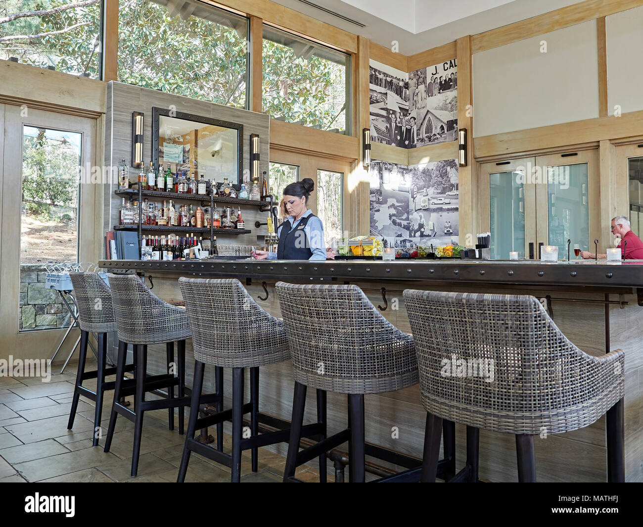 Empty bar stools with a female, or woman bartender standing behind the bar during the daytime. - Stock Image