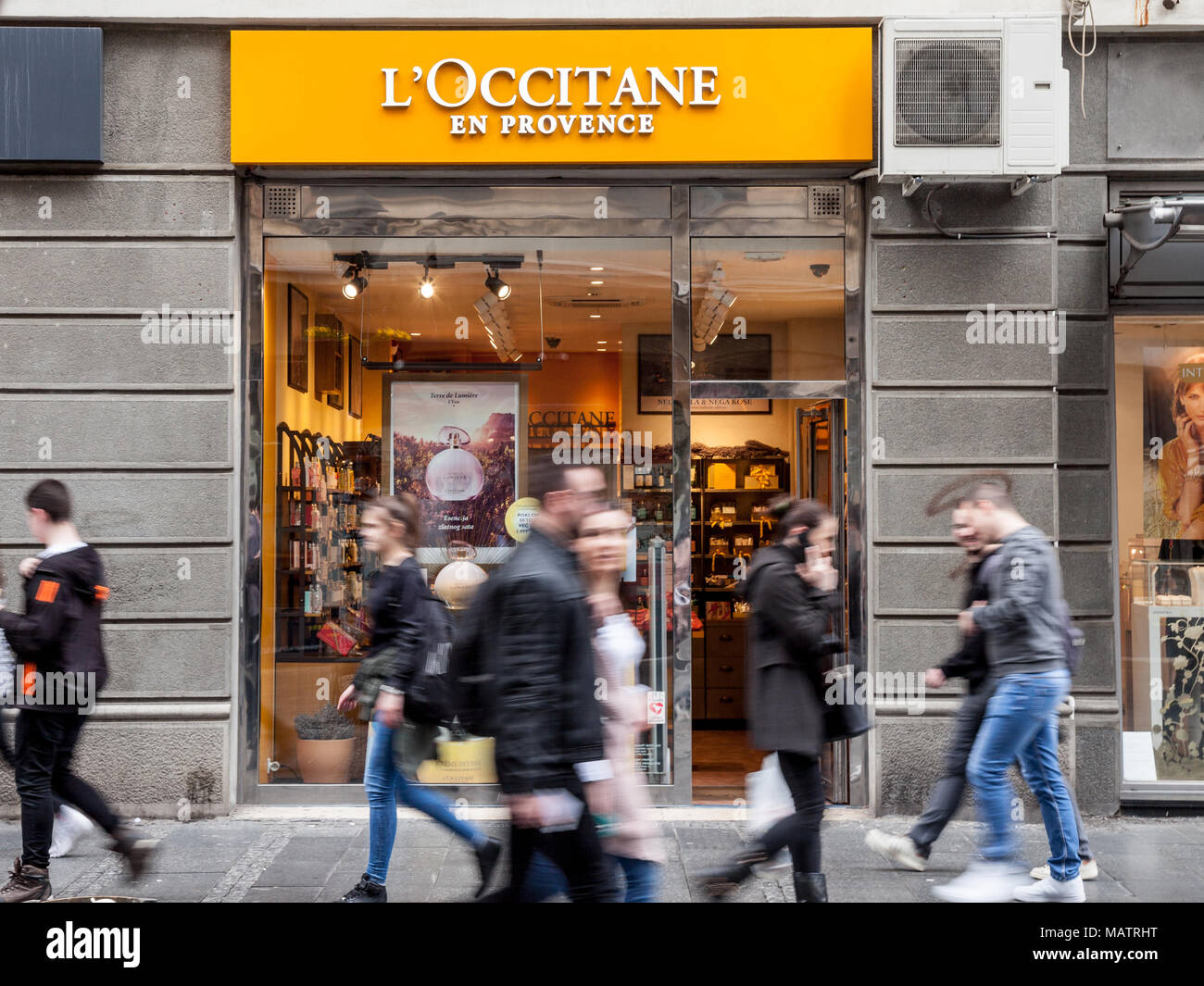 BELGRADE, SERBIA - MARCH 31, 2018: L'Occitane en Provence logo on their shop of Belgrade, people passing by. This brand is the most known Southern Fra - Stock Image