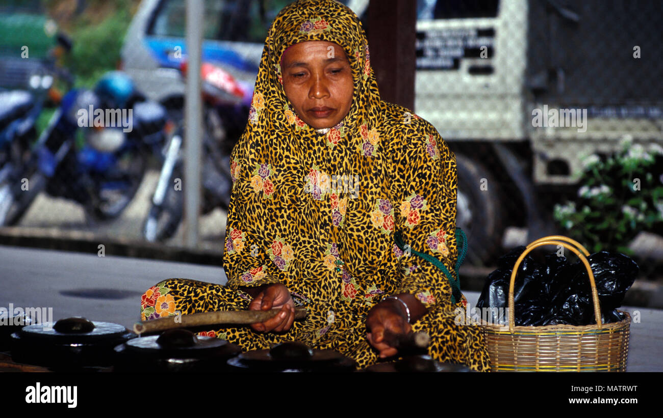 An indigenous Bajau woman becomes a one-piece gamelan orchestra while out shopping at the Kota Belud market in Sabah, Malaysia. - Stock Image