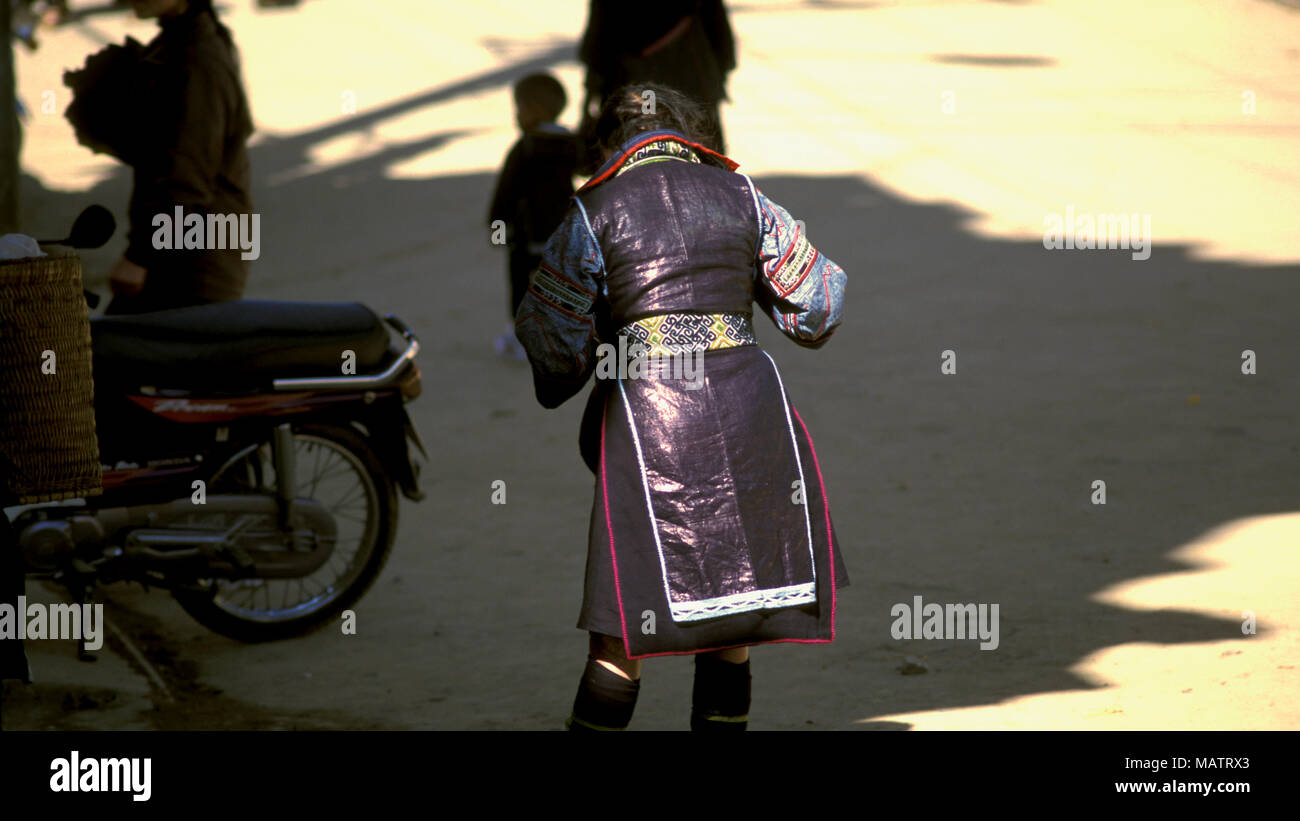 Late afternoon sunlight reflects off the traditional indigo-dyed dress of a young, indigenous H'mong (Hmong) girl in Sapa, Vietnam. - Stock Image