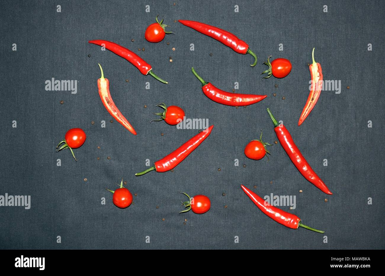 Hot chilli, pepper and tomatoes on black background, top view, minimalist style - Stock Image